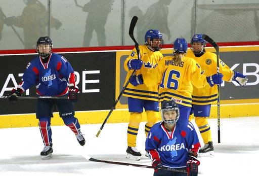 Sweden's players, in yellow, celebrate after scoring against combined Koreas during their women's ice hockey friendly game at Seonhak International Ice Rink in Incheon, South Korea, Sunday, Feb. 4, 2018. (Kim Hong-Ji/Pool Photo via AP)