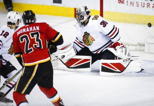 Chicago Blackhawks goalie Jeff Glass, right, looks back as Calgary Flames' Sean Monahan scores in overtime of an NHL hockey game Saturday, Feb. 3, 2018, in Calgary, Alberta. (Jeff McIntosh/The Canadian Press via AP)