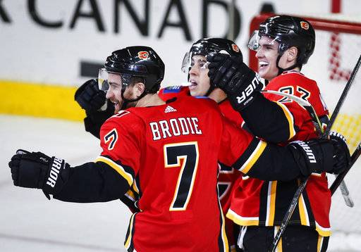 Calgary Flames' Sean Monahan, right, celebrates his game-winning goal with teammates T.J. Brodie, left, and Johnny Gaudreau during overtime in an NHL hockey game Saturday, Feb. 3, 2018, in Calgary, Alberta. (Jeff McIntosh/The Canadian Press via AP)