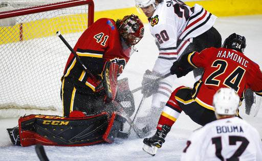 Chicago Blackhawks' Brandon Saad, center, has his shot blocked by Calgary Flames goalie Mike Smith during the second period of an NHL hockey game Saturday, Feb. 3, 2018, in Calgary, Alberta. Jeff McIntosh/The Canadian Press via AP