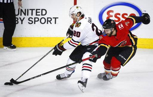 Chicago Blackhawks' Brandon Saad, gets past Calgary Flames' T.J. Brodie during the second period of an NHL hockey game in Calgary, Alberta, Saturday, Feb. 3, 2018. (Jeff McIntosh/The Canadian Press via AP)