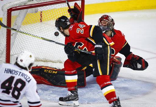Chicago Blackhawks' Vinnie Hinostroza, left, scores on Calgary Flames goalie Mike Smith, right, during the second period of an NHL hockey game in Calgary, Alberta, Saturday, Feb. 3, 2018. (Jeff McIntosh/The Canadian Press via AP)