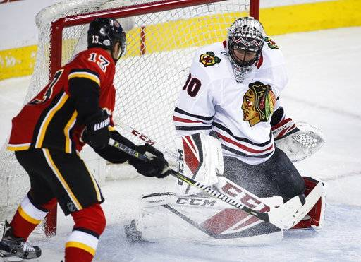Chicago Blackhawks goalie Jeff Glass, right, stop a shot from Calgary Flames' Johnny Gaudreau during the first period of an NHL hockey game in Calgary, Alberta, Saturday, Feb. 3, 2018. (Jeff McIntosh/The Canadian Press via AP)