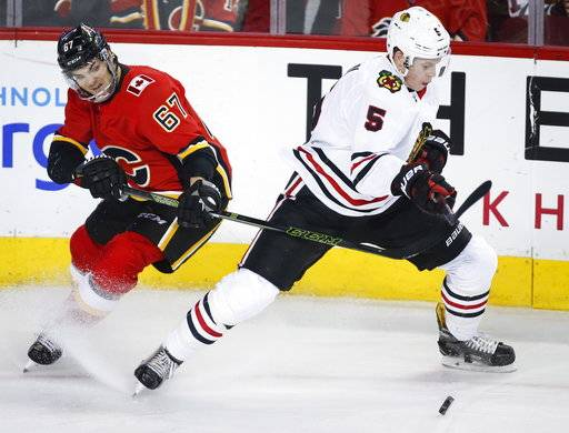 Chicago Blackhawks' Connor Murphy, right, escapes from Calgary Flames' Michael Frolik, from the Czech Republic, during the first period of an NHL hockey game in Calgary, Alberta, Saturday, Feb. 3, 2018. (Jeff McIntosh/The Canadian Press via AP)