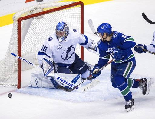 Tampa Bay Lightning goaltender Andrei Vasilevskiy (88) makes a save against Vancouver Canucks' Brock Boeser (6) during the third period of an NHL hockey game Saturday, Feb. 3, 2018, in Vancouver, British Columbia. (Ben Nelms/The Canadian Press via AP)
