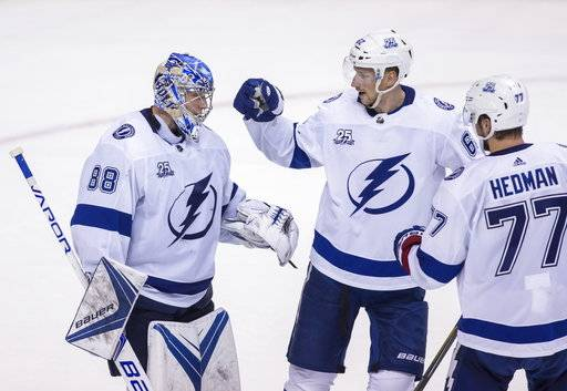 Tampa Bay Lightning goaltender Andrei Vasilevskiy (88) celebrates the team's win 4-2 over the Vancouver Canucks with Andrej Sustr (62) and Victor Hedman (77), after an NHL hockey game Saturday, Feb. 3, 2018, in Vancouver, British Columbia. (Ben Nelms/The Canadian Press via AP)