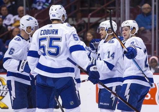 Tampa Bay Lightning's Chris Kunitz (14) celebrates his goal against the Vancouver Canucks with teammates Anton Stralman (6), Braydon Coburn (55) and Brayden Point (21) during first-period NHL hockey game action in Vancouver, British Columbia, Saturday, Feb. 3, 2018. (Ben Nelms/The Canadian Press via AP)