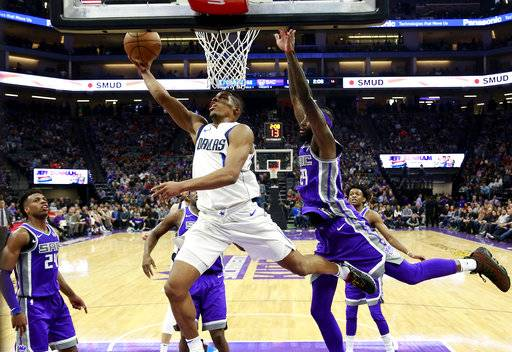 Dallas Mavericks guard Dennis Smith Jr., center, goes to the basket past Sacramento Kings forward JaKarr Sampson, right, during the first half of an NBA basketball game Saturday, Feb. 3, 2018, in Sacramento, Calif.