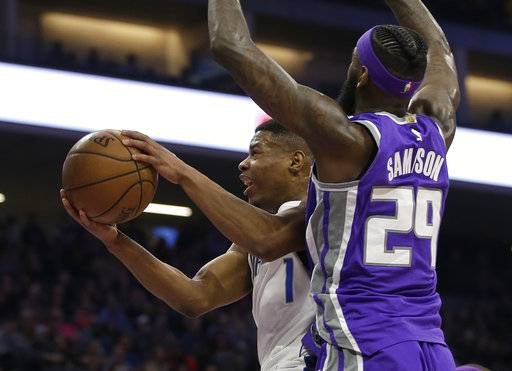 Dallas Mavericks guard Dennis Smith Jr., left, goes to the basket against Sacramento Kings forward JaKarr Sampson during the first half of an NBA basketball game Saturday, Feb. 3, 2018, in Sacramento, Calif.
