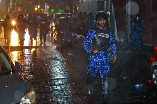 A Maldives policeman charges with baton towards protesters after the government declared a 15-day state of emergency in Male, Maldives, early Tuesday, Feb. 6, 2018. The Maldives government declared a 15-day state of emergency Monday as the political crisis deepened in the Indian Ocean nation amid an increasingly bitter standoff between the president and the Supreme Court. Hours after the emergency was declared, soldiers forced their way into the Supreme Court building, where the judges were believed to be taking shelter, said Ahmed Maloof, an opposition member of Parliament.
