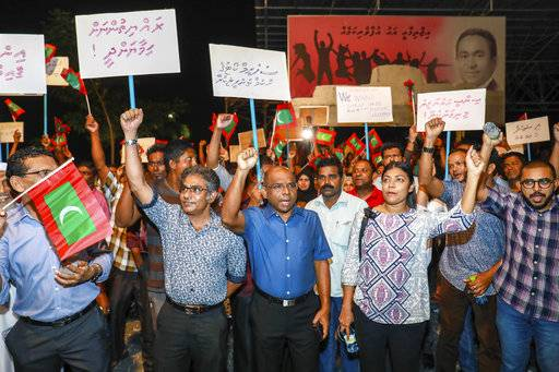 "In this late Sunday, Feb.4, 2018 photo, Maldivian opposition supporters shout slogans during a protest as they the urge the government to obey a Supreme Court order to release and retry political prisoners, including an ex-president in Male, Maldives. The political crisis in the Maldives deepened Monday, as the government of the island nation said it would not obey a Supreme Court order to free a group of imprisoned opposition leaders. Placards in Divehi language from left, to right, read, ""protect the citizens , carry out the supreme court's order, free political prisoners and to uphold justice""."