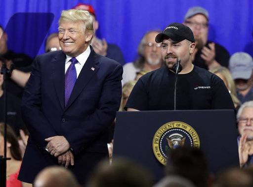 Tyler Berkshire, a machinist at Sheffer Corp., speaks as President Donald Trump listens during a speech on tax policy during a visit to Sheffer Corporation, Monday, Feb. 5, 2018, in Blue Ash, Ohio.