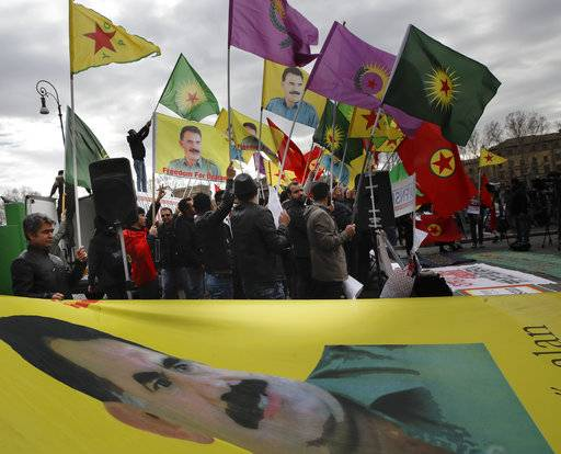 Demonstrators wave Turkish Workers' Party (PKK) flags bearing an image of PKK leader Abdullah Ocalan as they shout slogans during a sit-in near the Vatican in Rome, Monday, Feb. 5, 2018. Some 150 Kurdish protesters gathered near the Vatican on Monday as Turkish President Recip Tayyip Erdogan swept past in a long motorcade to the Vatican where he met with Pope Francis.