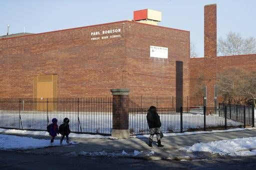 In this Jan. 18, 2018, photo,people walk past Paul Robeson High School in the Englewood neighborhood of Chicago. Five years after the nation's largest mass closure of public schools, Chicago is forging ahead with plans to shutter four more in one of the city's highest-crime and impoverished areas while school officials are pitching the closure and demolition of Robeson in Englewood to make way for a new $85 million school they insist will better serve students and reverse low enrollment.