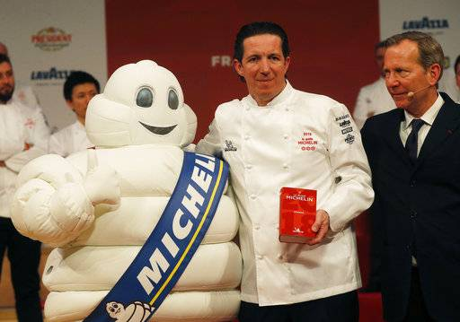 Three-star chef Christophe Bacquie at the Castellet Hotel, enter poses with Michelin Mascot known as Bibendum, left, and Michelin Guides Director Michael Ellis during the Michelin Guide ceremony in Boulogne-Billancourt, outside Paris, France, Monday, Feb. 5, 2018. A record 28 French restaurants were honored with the gastronomic world's most coveted prize Monday: a three-star Michelin rating.