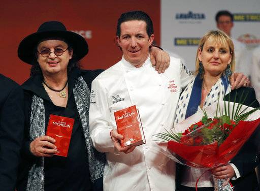 Three-star chefs Marc Veyrat of La Maison des Bois, left, Christophe Bacquie at the Castellet Hotel, center, and his wife Alexandra Bacquie pose during the Michelin Guide ceremony in Boulogne-Billancourt, outside Paris, France, Monday, Feb. 5, 2018. A record 28 French restaurants were honored with the gastronomic world's most coveted prize Monday: a three-star Michelin rating.