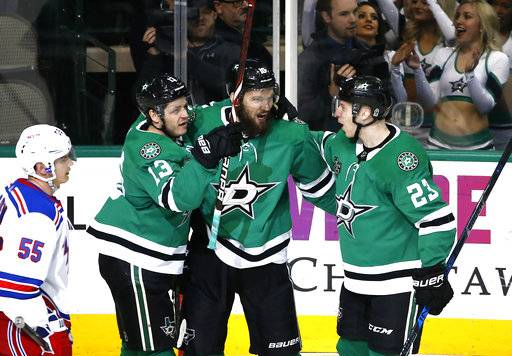 Dallas Stars center Mattias Janmark (13), center Martin Hanzal, middle, and defenseman Esa Lindell (23) celebrate following Hanzal's goal as New York Rangers defenseman Nick Holden (55) looks on during the third period of an NHL hockey game Monday, Feb. 5, 2018, in Dallas. The Stars won 2-1.