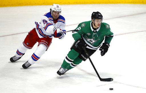 Dallas Stars defenseman Julius Honka (6) moves the puck as New York Rangers center Vinni Lettieri (95) tries to slow him down during the second period of an NHL hockey game Monday, Feb. 5, 2018, in Dallas.