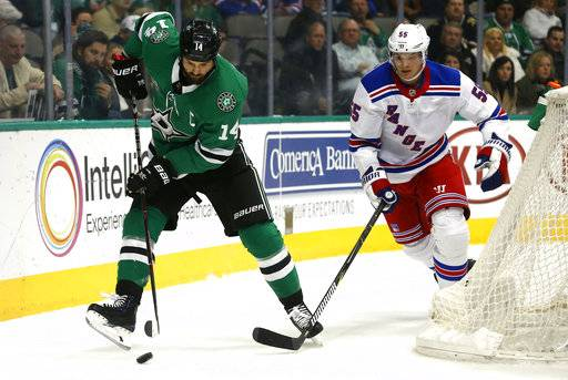 Dallas Stars left wing Jamie Benn (14) controls the puck as New York Rangers defenseman Nick Holden (55) moves in during the first period of an NHL hockey game Monday, Feb. 5, 2018, in Dallas.