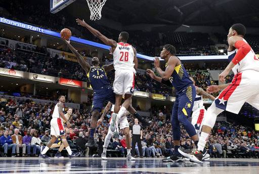 Indiana Pacers guard Lance Stephenson (1) shoots under Washington Wizards center Ian Mahinmi (28) during the second half of an NBA basketball game in Indianapolis, Monday, Feb. 5, 2018. The Washington Wizards defeated the Pacers 111-102.