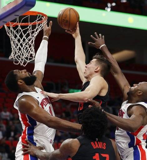 Detroit Pistons center Andre Drummond, left, prepares to swat the ball away from Portland Trail Blazers center Zach Collins (33) during the first half of an NBA basketball game, Monday, Feb. 5, 2018, in Detroit.
