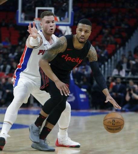 Detroit Pistons forward Blake Griffin, left, defends as Portland Trail Blazers guard Damian Lillard (0) dribbles during the first half of an NBA basketball game, Monday, Feb. 5, 2018, in Detroit.