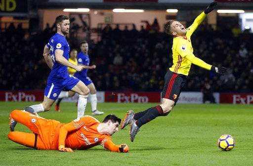 Chelsea's goalkeeper Thibaut Courtois, left, fouls Watford's Gerard Deulofeu, right, during the English Premier League soccer match between Watford and Chelsea at Vicarage Road stadium in London, Monday, Feb. 5, 2018.