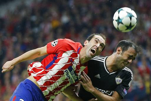 FILE - In this Tuesday, Oct. 31, 2017 file photo, Atletico's Diego Godin, left, and Qarabag's Elvin Ismayilov jump for the ball during a Group C Champions League soccer match between Atletico Madrid and Qarabag at the Metropolitano stadium in Madrid, Spain. Atletico Madrid says defender Diego Godin has undergone reconstructive procedure on his mouth after losing some of his teeth in a brutal collision in a Spanish league match Sunday Feb. 4, 2018.