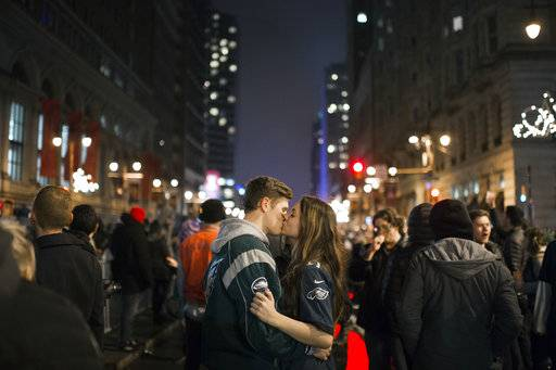 Julia Kauterman, right, and Michael Banes of Berlin, N.J. kiss on Broad Street as Eagles fans celebrate a Super Bowl win against the New England Patriots Sunday, Feb. 4, 2018, in Philadelphia. (Joe Lamberti /Camden Courier-Post via AP)