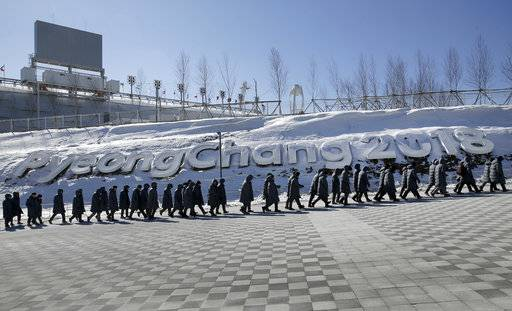 Workers walk up a ramp at the Pyeongchang Olympic Plaza as preparations continue for the 2018 Winter Olympics in Pyeongchang, South Korea, Monday, Feb. 5, 2018.