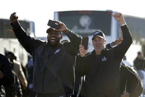 Philadelphia Eagles defensive tackle Fletcher Cox, left, and head coach Doug Pederson approach a fence where fans gathered to welcome the team Monday, Feb. 5, 2018, at Philadelphia International Airport a day after defeating the New England Patriots in Super Bowl 52.