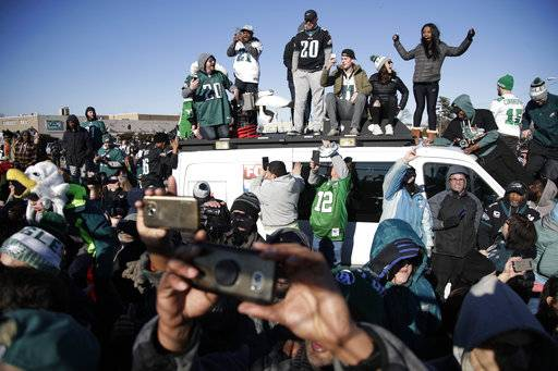 Philadelphia Eagles stand atop a news van while waiting for the team to deplane Monday, Feb. 5, 2018, at Philadelphia International Airport a day after defeating the New England Patriots in Super Bowl 52.