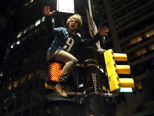 A Philadelphia Eagles fan celebrates the team's victory in the NFL Super Bowl 52 between the Philadelphia Eagles and the New England Patriots, Sunday, Feb. 4, 2018, in downtown Philadelphia.