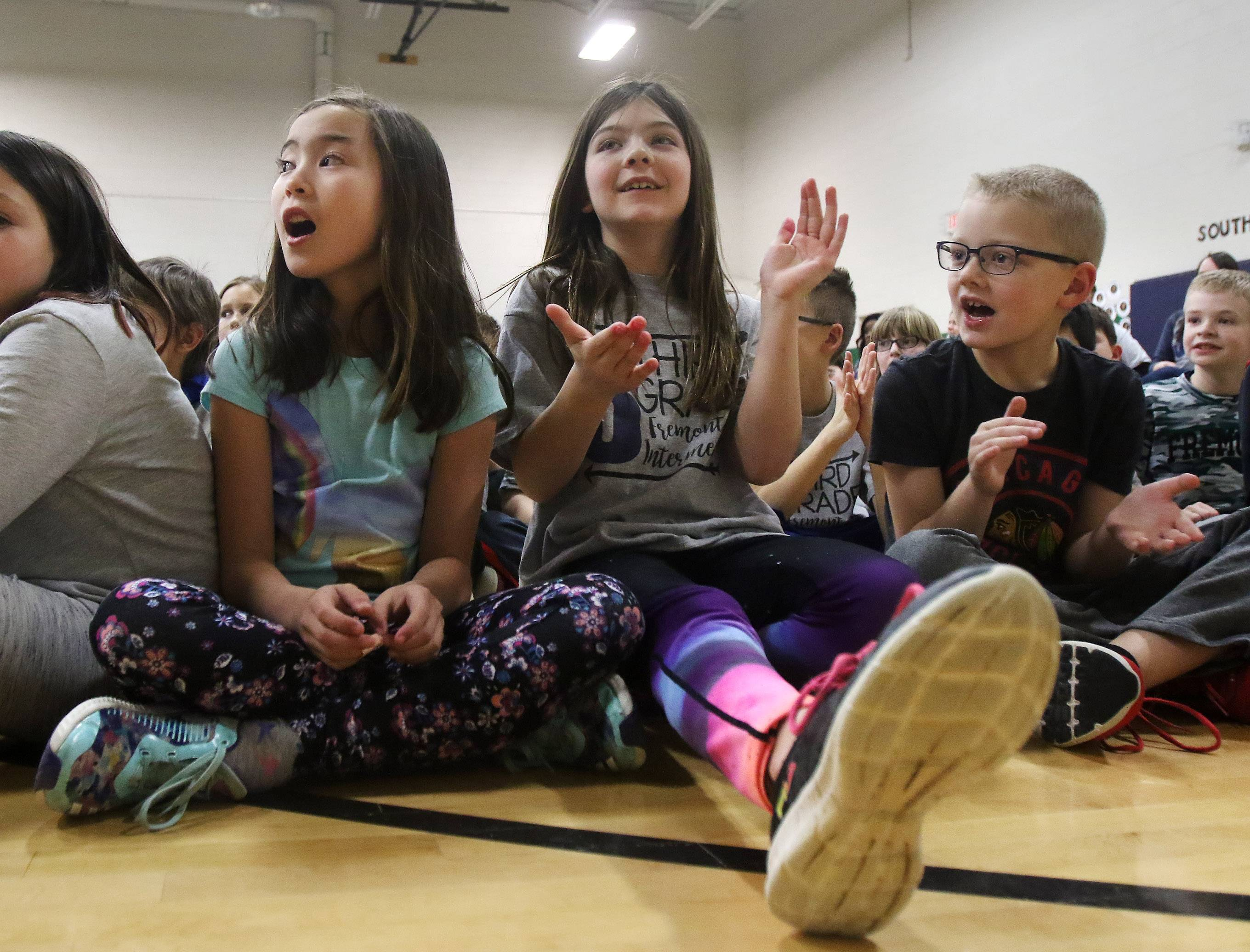 "Fremont Intermediate School third-graders Lyla Villaraza, left, Maddy Kerns and Ryan McNelly sing along with entertainer Stu Jacobson during his ""Be Kind, Be Positive, and Read!"" program Tuesday at the Mundelein-area school. The daytime talk show ""Windy City LIVE"" recorded him for an upcoming episode."