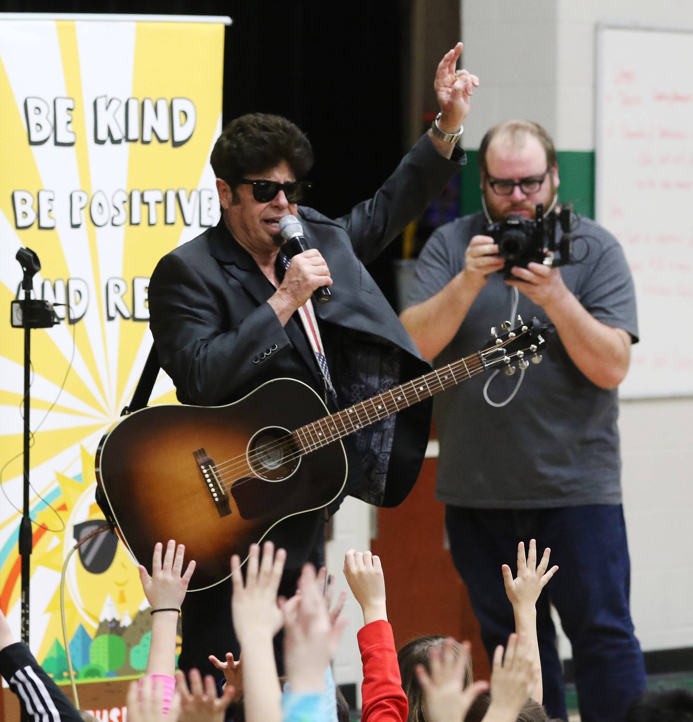 "Entertainer Stu Jacobson is filmed by videographer Brian Rich as he presents his program, ""Be Kind, Be Positive, and Read!"" for students at Fremont Intermediate School near Mundelein on Tuesday. The daytime talk show ""Windy City LIVE"" recorded him for an upcoming episode."