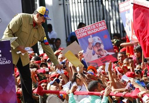 Venezuela's President Nicolas Maduro reaches for letters written by supporters during a rally marking the anniversary of the failed 1992 coup led by late President Hugo Chavez in Caracas, Venezuela, Sunday, Feb. 4, 2018. Maduro will run for reelection in this year's presidential election.
