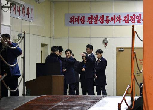 "South Korean customs officials board the North Korean ship Mangyongbong-92 carrying art troupe members on its arrival at Mukho port in Donghae, South Korea Tuesday, Feb. 6, 2018. The art troupe, led by Hyon Song Wol, also the leader of the famous Moranbong girl band hand-picked by North Korean leader Kim Jong Un, will perform in Gangneung and Seoul on Feb. 8 and Feb. 11, respectively, before returning home. The banners read "" Greater Kim Il Sung and Kim Jong Il."" (Song Kyung-Seok/Pool Photo via AP)"