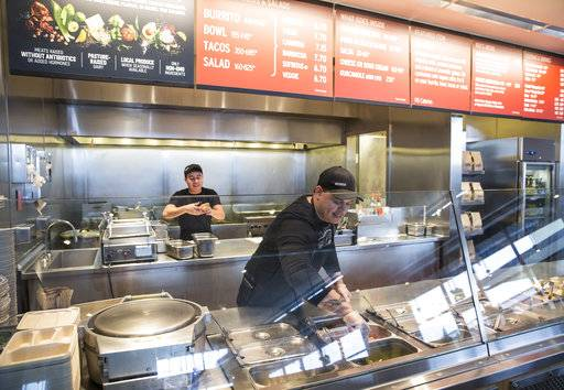 FILE - In this Tuesday Dec. 15, 2015, file photo, a Chipotle Mexican Grill employee prepares food in Seattle. Chipotle Mexican Grill Inc. reports quarterly financial results, Tuesday, Feb. 6, 2018.