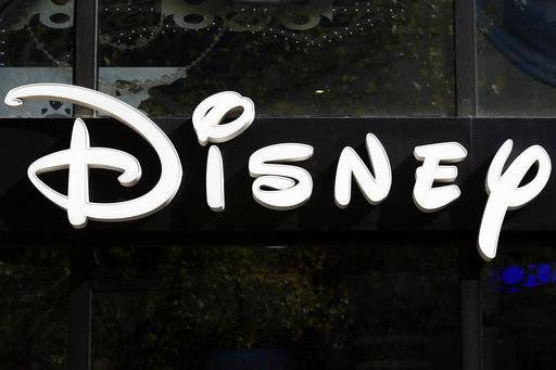 FILE - This Sept. 20, 2017, file photo shows a sign at the Disney store on the Champs Elysees Avenue in Paris, France. The Walt Disney Co. reports earnings Tuesday, Feb. 6, 2018.