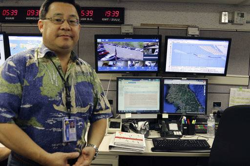 FILE - In this July 21, 2017 file photo, Jeffrey Wong, the Hawaii Emergency Management Agency's operations officer, shows computer screens monitoring hazards at the agency's headquarters in Honolulu. The photo originally accompanied an Associated Press story in July about Hawaii preparing for a missile threat from North Korea. Some online news organizations used the AP photo in their coverage of the Jan. 13, 2018 false missile alert in Hawaii, leading some people to believe Wong was the person who sent the false alert. The AP did not use the image in coverage of the false alert. Wong says he has received threats and harassment because of the use of the image online.