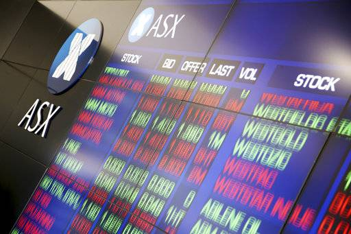 A display board at the Australian Stock Exchange changes listings in Sydney, Wednesday, Feb. 7, 2018. Major indexes in Asia and Europe Tuesday took steep losses and U.S. markets started sharply lower, only to repeatedly change direction.