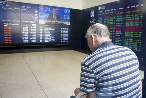 A man watches display boards at the Australian Stock Exchange in Sydney, Wednesday, Feb. 7, 2018. Major indexes in Asia and Europe Tuesday took steep losses and U.S. markets started sharply lower, only to repeatedly change direction.