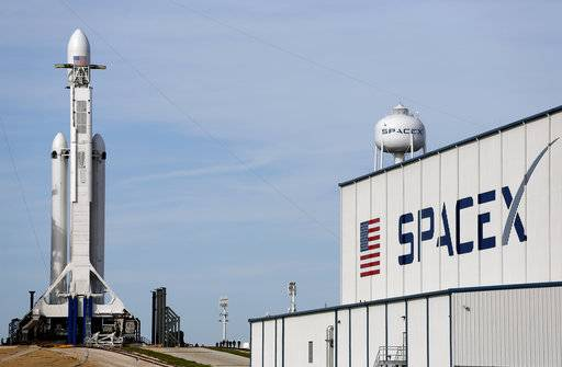 A Falcon 9 SpaceX heavy rocket stands ready for launch on pad 39A at the Kennedy Space Center in Cape Canaveral, Fla., Monday, Feb. 5, 2018. The Falcon Heavy scheduled to launch Tuesday afternoon, has three first-stage boosters, strapped together with 27 engines in all.