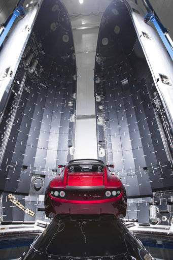 This Dec. 6, 2017 photo made available by SpaceX shows a Tesla car next to the fairing of a Falcon Heavy rocket in Cape Canaveral, Fla. For the Heavy's inaugural flight, the rocket will carry up Elon Musk's roadster. In addition to SpaceX, Musk runs the electric car maker Tesla.  (SpaceX via AP)