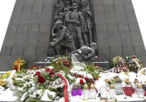 Snow covers flowers at the Warsaw Ghetto Uprising memorial in Warsaw, Poland, Tuesday, Feb. 6, 2018. Poland's president Andrzej Duda said Tuesday he will sign into law a controversial proposal to outlaw blaming Poland as a nation for crimes committed by Nazi Germany during the Holocaust, despite strong criticism from Israel and the United States, but he will ask the country's constitutional court to evaluate the bill.