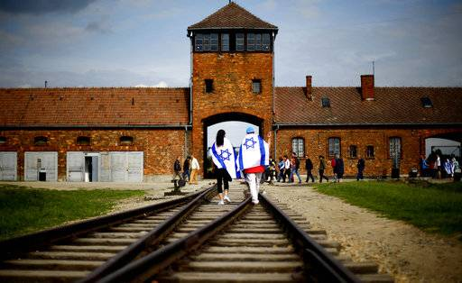 FILE- This June 25, 2015 file picture shows Brzezinka or Birkenau nazi death camp near Oswieciem, Poland, when young visitors with Israeli flags walk on railway tracks on the grounds of the former German Nazi death camp Auschwitz-Birkenau. The office of Polish President Andrzej Duda said the leader will on Tuesday, Feb. 6, 2018 announce his decision on whether to sign legislation penalizing certain statements about the Holocaust.