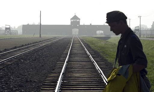FILE - In this July 29, 2016 file photo a man crosses the iconic rails leading to the former Nazi death camp of Auschwitz-Birkenau prior to a visit by Pope Francis, in Poland. The office of Polish President Andrzej Duda said the leader will on Tuesday, Feb. 6, 2018 announce his decision on whether to sign legislation penalizing certain statements about the Holocaust.