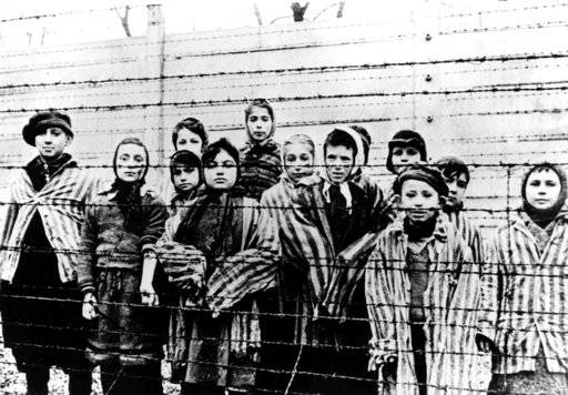 FILE - The file picture taken just after the liberation by the Soviet army in January, 1945, shows a group of children wearing concentration camp uniforms including Martha Weiss who was ten years-old, 6th from right, at the time behind barbed wire fencing in the Oswiecim (Auschwitz) Nazi concentration camp. The office of Polish President Andrzej Duda said the leader will on Tuesday, Feb. 6, 2018 announce his decision on whether to sign legislation penalizing certain statements about the Holocaust.