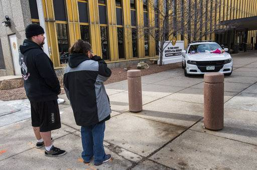 Karla Gross of Colorado Springs wipes away a tear as she and Joseph Gatelein pays their respects at a memorial outside the El Paso County Sheriff's Office in Colorado Springs, Colo., Tuesday, Feb. 6, 2018, for deputy Micah Flick, who was killed when an investigation of a motor vehicle theft turned into a deadly shooting Monday outside a Colorado Springs apartment complex. Three other law enforcement officers were shot. The suspect was killed and one citizen injured.  (Christian Murdock/The Gazette via AP)