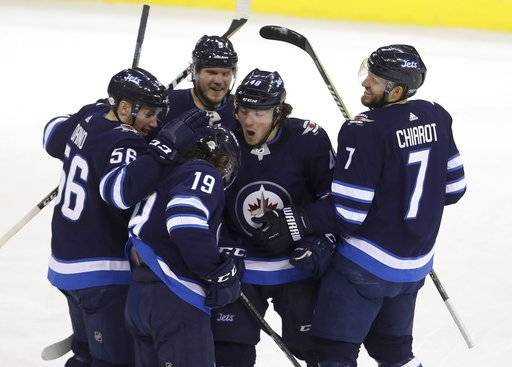 Winnipeg Jets' Marko Dano (56), Nic Petan (19), Dmitry Kulikov (5), Brendan Lemieux (48) and Ben Chiarot (7) celebrate after Petan scored against the Arizona Coyotes' during first period NHL hockey action in Winnipeg, Manitoba Tuesday, Feb. 6, 2018. (Trevor Hagan/The Canadian Press via AP)